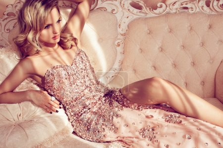 Photo for Luxurious blonde in a shiny dress on a sofa - Royalty Free Image