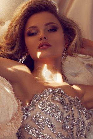 Photo pour Luxueux blonde vêtue d'une robe brillante sur un canapé - image libre de droit