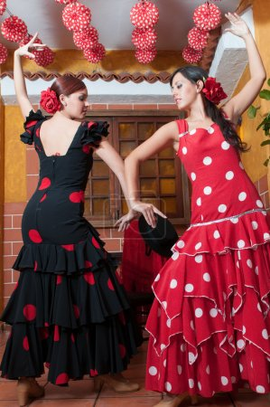 Photo for Women and man in traditional flamenco dresses dance during the Feria de Abril on April Spain - Royalty Free Image