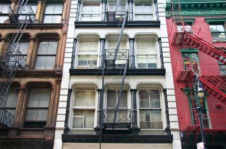 Photo pour Trois façades colorées, rouge, brun et blanc, immeubles d'habitation avec des évasions d'urgence. complexes de location new-yorkaise typique avec des escaliers de secours à côté des fenêtres. - image libre de droit