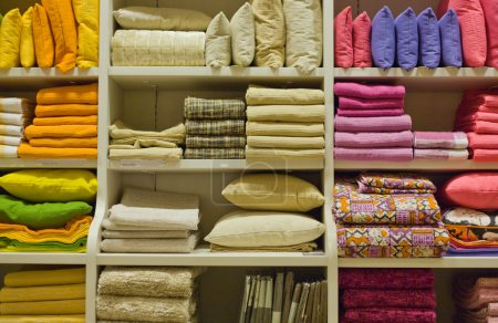 Photo for Bright pillows, towels, plaids, blankets and other home wear on shelves - Royalty Free Image