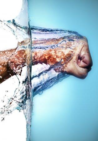 Photo pour Isolé caucasien mâle poing frapper bleu eau et éclaboussures gouttes sur un fond blanc - image libre de droit