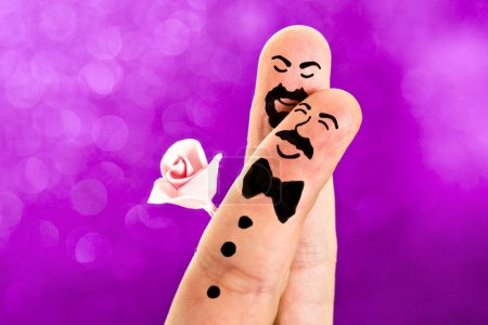 Fingers with sweet faces painted featuring a gay w...