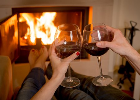Photo for Close up of young couple drinking wine in front of an open wood fire. - Royalty Free Image