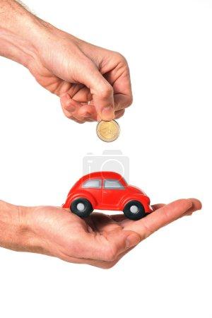 man inserting coin into mini car piggy bank
