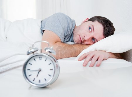 Photo for Young man in bed with eyes opened suffering insomnia and sleep disorder thinking about his problem - Royalty Free Image