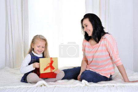 Happy attractive young mother giving present to cute blonde little daughter