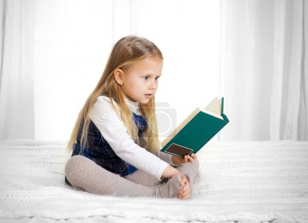 Scared cute blonde haired school girl reading a book