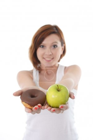 Young sport Woman with Apple and Chocolate Donut in Hands in healthy versus junk food dessert choice isolated on White background