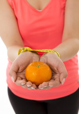 Woman's hands handcuffed together with a measuring tape with orange