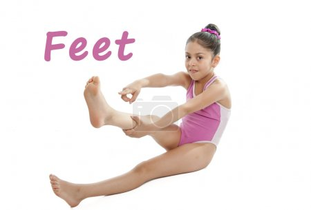 Photo for Girl wearing a pink swimsuit pointing at her feet on a white background for a school anatomy or body part chart - Royalty Free Image