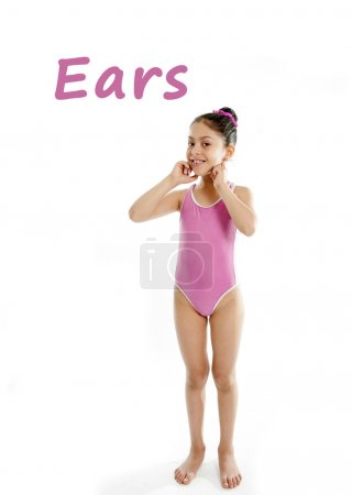 Photo for Full length of girl wearing a pink swimsuit pointing at her ears on a white background for a school anatomy or body part chart - Royalty Free Image