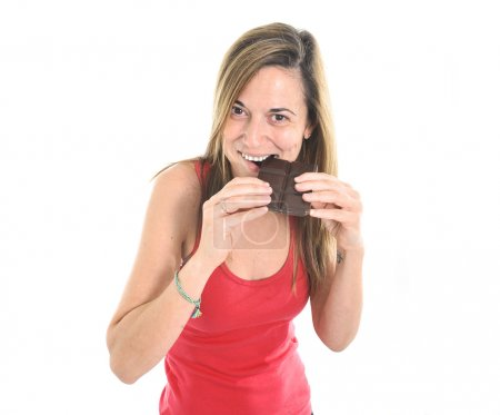Woman in sport clothes eating big chocolate bar forgetting about diet