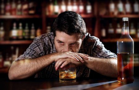 Photo for Young alcoholic drunk man thoughtful about alcohol addiction drinking indoors at bar of an irish pub leaning hands on whiskey glass in alcoholism concept - Royalty Free Image