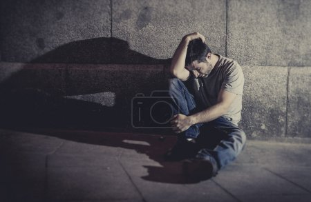 Photo for White wasted young man sitting on street ground with shadow on concrete wall feeling miserable and sad in urban scene representing depression and sickness - Royalty Free Image