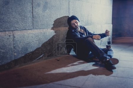 Photo for Urban scene of young alcoholic grunge man sitting on ground street corner drinking alcohol bottle with shadow on concrete wall in edgy lighting at night in the city - Royalty Free Image