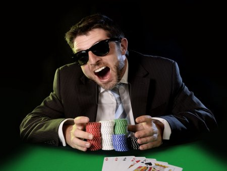 happy young attractive man grabbing poker chips after winning bet gambling