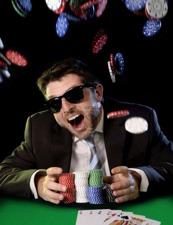 Photo pour Parie que heureux jeune homme séduisant, saisissant des jetons de poker après avoir remporté le jeu sur table avec les cartes à jouer sur le feutre vert au casino avec beaucoup de jetons volent tout autour isolée sur fond noir - image libre de droit