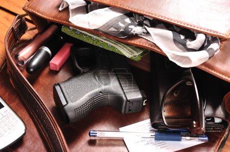 Photo pour Une arme à feu dans un sac à main - image libre de droit