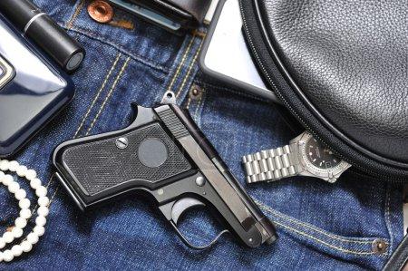 Photo pour Sac à main d'une femme et pistolet et accessoires - image libre de droit