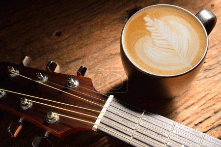 Photo pour Une tasse de café au lait et de la guitare sur une table en bois. - image libre de droit