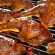 Grilled chicken thighs on the flaming grill.