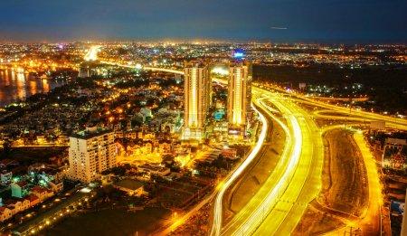 Photo pour Incroyable paysage nocturne de Ho chi Minh-ville, Vietnam de haute vue, ville lumineuse en lumière électrique jaune, sentier sur la route, paysage de nouvelle ville aux couleurs éclatantes la nuit - image libre de droit