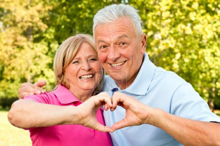 Photo for Senior healthy couple showing heart and smiling outdoor - Royalty Free Image