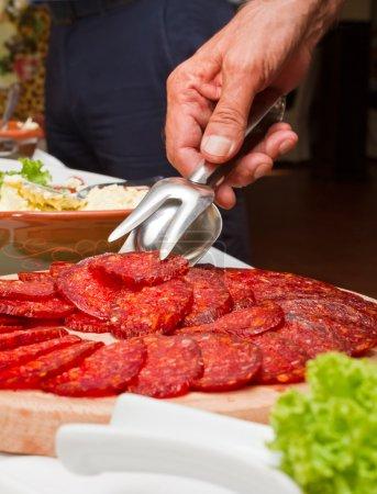 Photo pour Pince à main humaine sur une assiette de salami tranché - image libre de droit