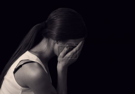 Photo for Young female expressing sadness and sorrow on black background - Royalty Free Image