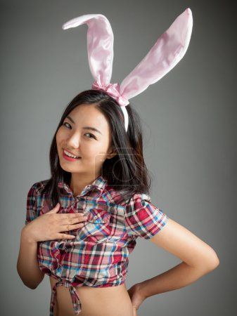 Portrait of sexy asian cowgirl wearing easter's bunny ears