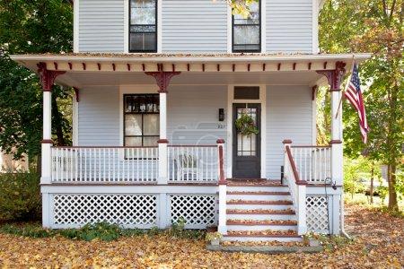 Photo pour Vue frontale d'une maison américaine avec des feuilles tombées sur les escaliers et agitant le drapeau des États-Unis près de la porte. Chicago . - image libre de droit