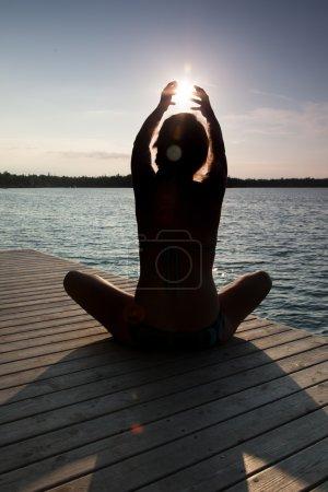 Photo pour Silhouette d'une femme assise en position lotus sur une jetée en bois avec du soleil dans les mains - image libre de droit