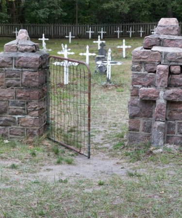 Photo for White crosses with with brick fence on foreground  in the cemetery closeup. - Royalty Free Image