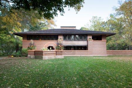 Photo pour Vue de la maison de deux étages sur la pelouse verte avec des feuilles tombées . - image libre de droit