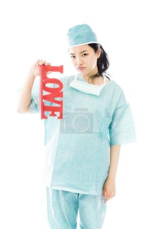 """Surgeon holding """"LOVE"""" text"""
