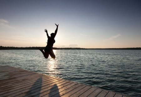 Silhouette of a woman jumping in a bay