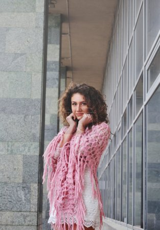 Cute curly hair girl standing near wall smiling