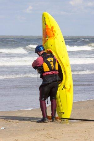 Man ready to lift kayak on the beach