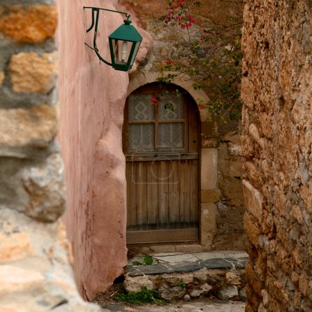 Wooden door in a Greek town of Monamvasia with an old lamp above entrance. Clay and stone walls surrounding stairs leading to the door.