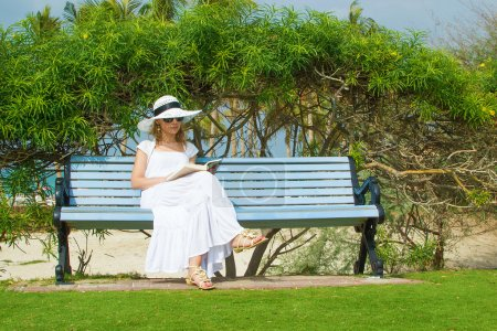 Sexy woman reading in the park next to the beach