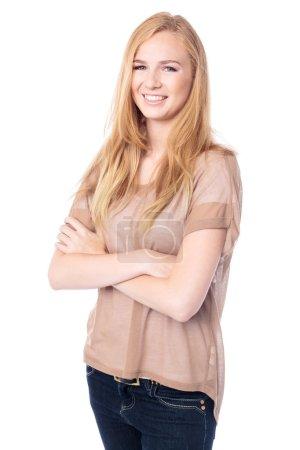 Foto de Hermosa mujer rubia con los brazos cruzados de pie en un ángulo sonriendo a la cámara con una sonrisa encantadora, aislada en blanco - Imagen libre de derechos