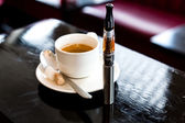 Espresso coffee with an e-cigarette in a pub