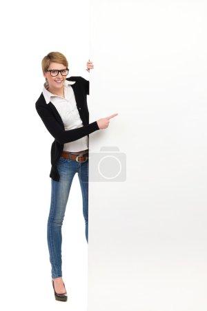 Photo pour Femme blonde à lunettes tenant bannière et pointant à l'espace copie. studio pleine longueur tir isolé sur blanc. - image libre de droit