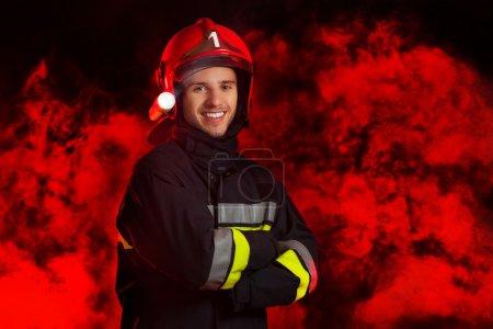 Fireman posing against red smoke.