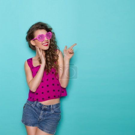 Photo for Smiling young woman in heart shaped glasses is pointing at copy space. Three quarter length studio shot on teal background. - Royalty Free Image