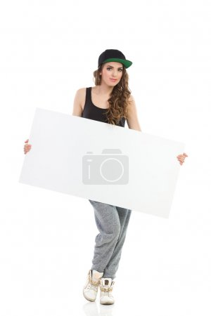 Photo for Cool young woman in gray track-suit and full cap posing with blank placard. Full length studio shot isolated on white. - Royalty Free Image