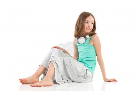 Photo for Young girl with headphones on her neck is sitting on the floor and looking away. Full length studio shot isolated on white. - Royalty Free Image
