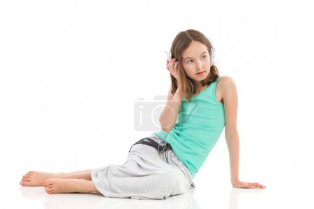 Photo for Little girl with headphones is sitting on the floor and listening to the music. Full length studio shot isolated on white. - Royalty Free Image