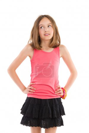 Photo pour Petite fille posant les mains sur la hanche et regardant ailleurs. Trois quarts studio tourné isolé sur blanc . - image libre de droit